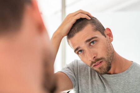 Jeune homme mal rasé regardant le miroir dans la salle de bain à la maison. Beau mec regardant son visage dans un miroir, vérifiant les cheveux et la racine des cheveux. Homme en pyjama concerné par la perte de cheveux.
