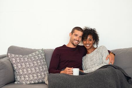 Happy multiethnic couple sitting on sofa with warm blanket, enjoying hot cup of tea. Young man and african woman embracing on couch in winter and looking at camera. Portrait of young couple in love hugging on sofa with copy space. Stock Photo