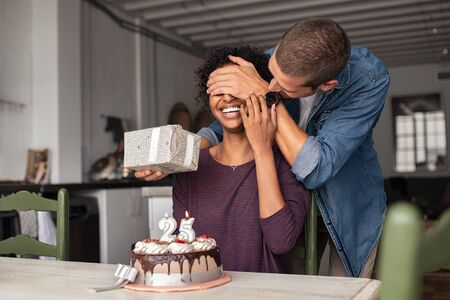 Young man giving present to his beloved girlfriend on birthday with cake on table. Cheerful african woman surprised by man during her 25th birthday. Guy covering girl eyes while surprising her with ca
