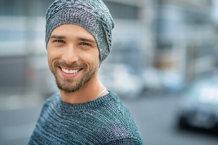 Portrait of smiling man wearing woolen cap outdoor. Handsome young man in winter clothes looking at camera. Closeup face of cheerful guy wearing sweater in winter with copy space.
