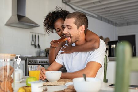 African american woman embracing from behind her boyfriend and feeding him with brown bread and jam. Multiethnic couple enjoying breakfast at home. Beautiful laughing woman feeding young man in kitche