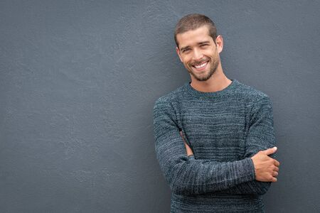 Portrait of happy young man leaning against wall isolated on grey background with a big smile. Handsome cheerful guy in winter clothes on gray wall looking at camera. Stylish man wearing sweater with  写真素材