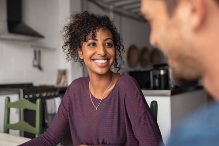 Smiling african american woman with man at home in conversation. Beautiful young loving wife talking to husband in living room. Portrait of happy black girl with curly hair sitting at table and talkin