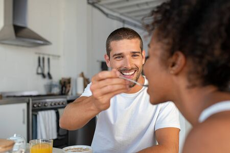 Happy multiethnic couple having breakfast in kitchen. Smiling handsome man feeding milk and cereal to woman in the morning. Girlfriend enjoying being pampered by boyfriend.