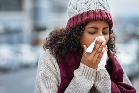 Pretty black woman blowing her nose with a tissue outdoor in winter. Young african woman getting sick with flu in a winter day. Woman with a cold rubs nose with handkerchief. Stock Photo