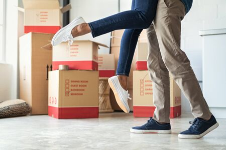 Man lifting his girlfriend among cardboard boxes as they start living together in new house. Closeup of excited husband embracing wife celebrating relocation. Loving man standing near boxes lifting wo 写真素材