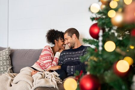 Young happy couple embracing and relaxing on comfortable couch. Lovely multiethnic couple sitting on sofa wearing christmas sweater and hugging. African woman and affectionate man near christmas tree.