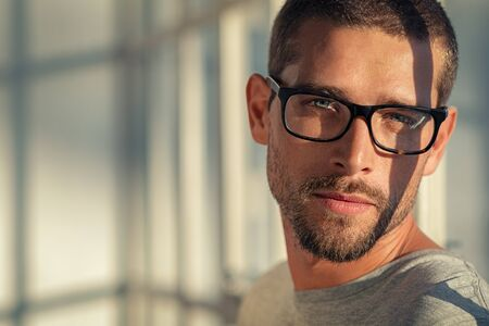 Portrait of stylish young man wearing eyeglasses at home. Closeup face of handsome guy wearing spectacles with sunlight and shadow reflection on face. Portrait of satisfied cool man in casual looking