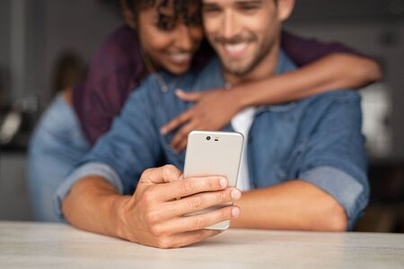 Happy couple using smartphone at home. Closeup of smiling man holding smartphone while african woman embracing him in background. Couple sharing media on smart phone. 写真素材