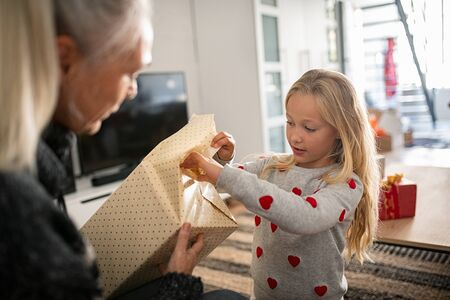 Little girl wearing sweater and opening christmas present at home. Curious granddaughter open birthday present with grandmother. Child unwrapping xmas gift with mother.