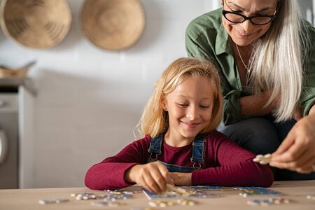 Grandmother and granddaughter doing jigsaw puzzle together at home. Senior woman helping smiling little girl to solve puzzles. Happy grandchild with concentration solving jigsaw puzzle at home while l