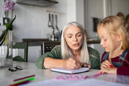 Beautiful senior woman helping little girl with homework. Old grandmother showing granddaughter how to solve a math problem. Teacher teaching little girl at home and writing on notebook.