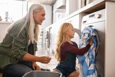 Smiling senior woman with cute girl loading washing machine at home. Grandmother and granddaughter putting dirty clothes into washing machine. Little happy grandchild sitting on floor helping granny d