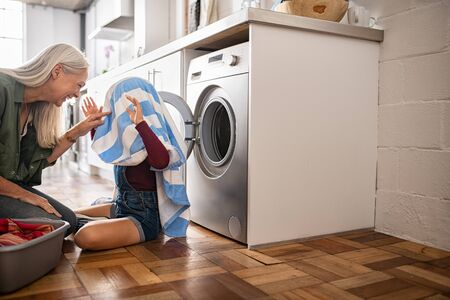 Child hiding in blue and striped towel scaring mature woman near washing machine at home. Smiling old grandmother and funnny little girl playing with fresh laundry clothes on floor. Grandchild plays t 写真素材
