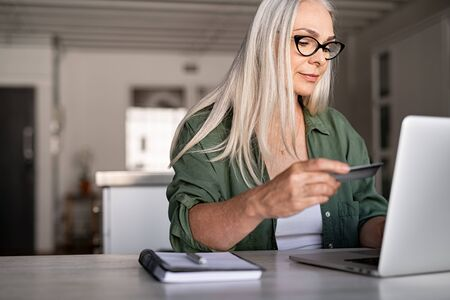 Mature woman using credit card making online payment at home. Successful old woman doing online shopping using laptop. Closeup of retired fashionable lady holding debit card for internet banking accou