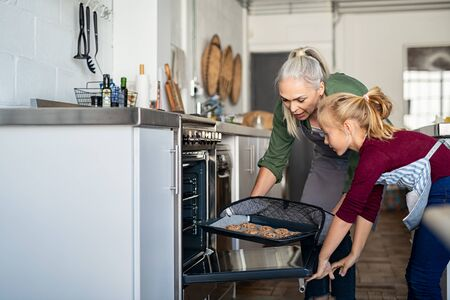 Mature grandmother wearing oven mitts and removing chocolate cookies from oven with granddaughter. Senior grandma taking hot bakeed biscuits out of the oven in kitchen. Old woman and little girl cooki