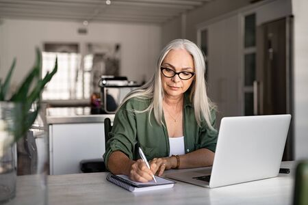 Senior stylish woman taking notes in notebook while using laptop at home. Old freelancer writing details on book while working on laptop in living room. Focused cool lady writing notary in notepad. 写真素材