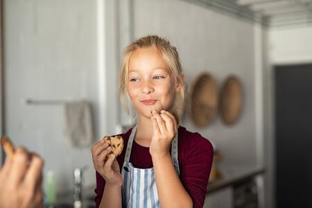 Cheerful little girl tasting chocolate chip cookies. Girl wearing apron and eating chocolate chip cookie in kitchen with grandmother. Happy girl enjoying self made biscuits at home with funny expression. Banque d'images