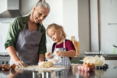 Little cute girl adding milk in dough. Granddaughter with old grandmother measuring milk for cookie dough. Focused child helping mature grandma in apron to prepare a cake in kitchen. 写真素材