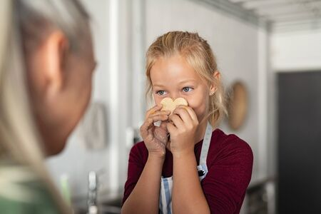 Cute little girl covering face with heart shaped cookie and looking her grandmother. Granddaughter playing while preparing cookies at home with granny. Funny girl showing uncooked biscuit near face to