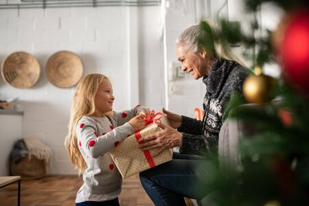 Happy senior woman giving christmas surprise to little girl at home. Excited granddaughter unpacking present under christams tree with old granny in sweater. Grandmother giving xmas gift to grandchild.