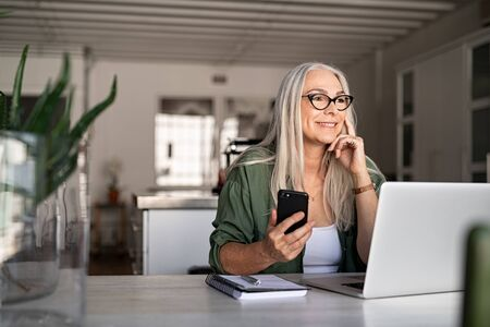 Happy senior woman holding smartphone and laptop daydreaming while looking away. Successful stylish old woman working at home while thinking about a good future. Cheerful fashionable lady entrepreneur 写真素材