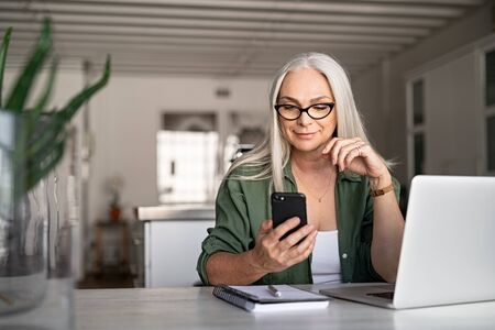 Happy senior woman using mobile phone while working at home with laptop. Smiling cool old woman with white hair wearing eyeglasses sitting on chair at table and messaging with smartphone. Beautiful st