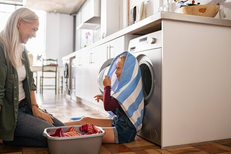 Mature woman and little granddaughter playing at home on laundry day. Cute little girl playing at home with smiling grandmother sitting in front of washing machine. Child hiding face with towel near w 写真素材