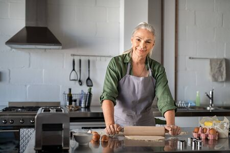Portrait of happy mature woman making dough at home. Portrait of housewife flattening cookie dough using wooden rolling pin in kitchen while smiling and looking at camera. Old woman preparing cookies. 写真素材