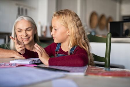 Child counting addition and subtraction on fingers while doing math homework. Elementary student with grandmother solving multiplication table in notebook and counting on fingers. Granny helping grand