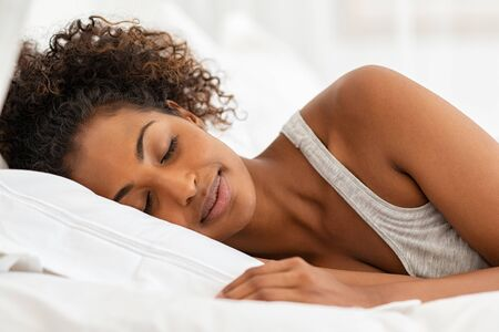 Beautiful young woman sleeping on bed in bedroom. African girl sleeping in her bed in the morning with eyes closed. Carefree black woman lying down on bed and dreaming. 版權商用圖片