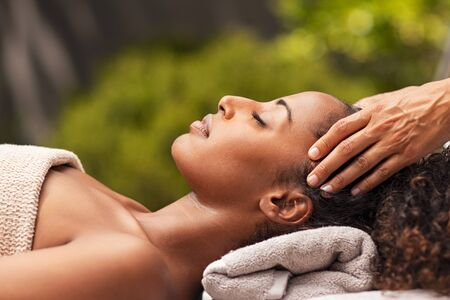 Beautiful black woman getting face massage in luxury spa. African american girl relaxing in resort spa while getting head massage. Masseuse hands massaging beauty black woman with closed eyes at outdoor spa.