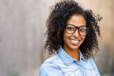 Happy smiling young woman with eyeglasses and denim shirt looking at camera. Black girl feeling successful standing against wall with copy space. African student smiling and wearing spectacles with curly hair.