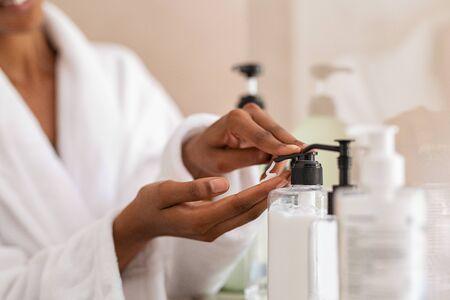 Manos de mujer africana con jabón líquido cosmético en el baño. Cerca de las manos negras de la niña en bata de baño con dispensador de loción corporal después de la ducha. Chica negra poniendo pomada en la mano de la bomba. Foto de archivo