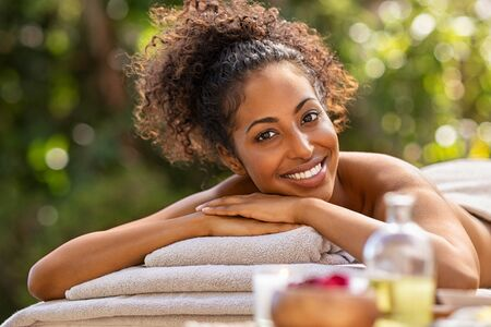 Closeup of a young woman in outdoor spa resort for massage therapy. Portrait of beautiful african american girl lying down on massage table outdoor. Smiling lady looking at camera while awaiting beaut