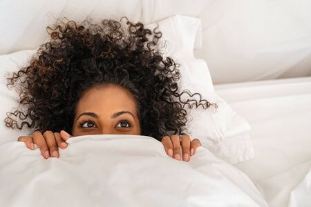 Funny young woman lying in bed and hiding under sheet while looking up with copy space. Top view of african american girl hiding face under white blanket on bed in the morning. Close up portrait of beautiful woman with curly hair covering face with bed sheet.