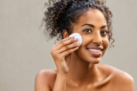 Young pretty african american woman taking off her makeup with cotton wipe sponge. Smiling girl cleaning face with cotton pad isolated over background. Black young woman cleansing face, daily healthy beauty routine.
