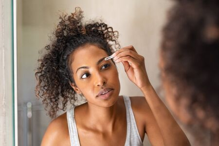 African american woman plucking eyebrows with tweezers while standing in front of the mirror. Closeup of young woman in pajamas removing facial hair in bathroom. Girl getting her eyebrows shaped during her morning beauty routine.