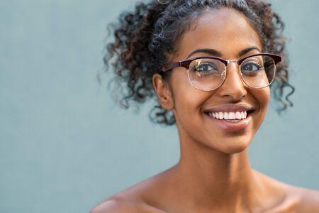Mujer joven alegre con hombro usando anteojos y mirando a cámara. Sonriente mujer afroamericana con pelo rizado con gafas aisladas sobre fondo azul. Retrato de niña negra feliz con espacio de copia.