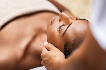 Beautiful african woman getting face massage in beauty spa. Black girl with closed eyes relaxing in outdoor spa while getting head massage. Serene woman relaxing outdoor in a beauty center. 版權商用圖片