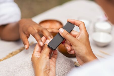 Close up of african hands of a qualified manicurist filing the nails of a young woman. Hands during manicure care session. Detail of a girl in a nail salon receiving manicure.