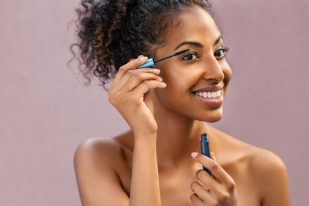 African woman applying black mascara on eyelashes with brush. Young beautiful woman applying makeup on eyes while looking at mirror. Portrait of black beauty girl applying makeup isolated over background with copy space. Stok Fotoğraf