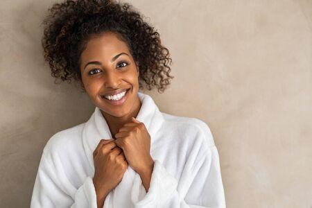 Fröhliche, freundliche junge Frau im weißen Bademantel, die die Kamera einzeln auf beigefarbenem Hintergrund mit Kopienraum betrachtet. Porträt des afroamerikanischen Mädchens im weißen Bademantel nach der Körperbehandlung. Fröhliche schwarze Dame mit lockigem Haar nach der Dusche. Standard-Bild