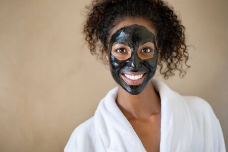 Smiling young woman with charcoal face mud looking at camera isolated on beige background with copy space. Portrait of african woman with curly hair wearing white bath robe getting black purifying mask at spa. Happy girl feeling relaxed at salon after face beauty facial treatment with peeling scrub clay. 免版税图像