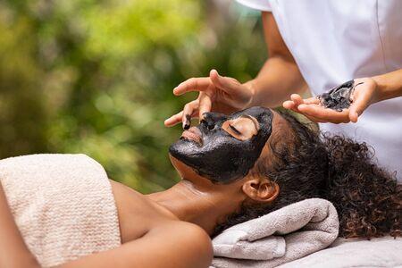 Giovane donna africana che riposa con gli occhi chiusi nella spa mentre la massaggiatrice applica la maschera facciale al carbone. Ragazza che si rilassa nella spa con fango nero sul viso per trattamenti di bellezza. Estetista che applica maschera peeling sul viso. Archivio Fotografico