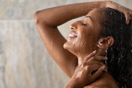 Young woman taking a hot shower relaxing under warm running water. Smiling beautiful black woman enjoy during hot water bath. Happy girl with closed eyes in shower rinse shampoo with water dripping on face. 版權商用圖片