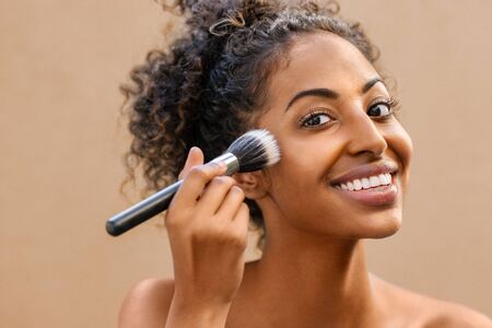 Closeup portrait of african woman applying foundation with makeup brush. Black beauty girl gets blush on the cheek isolated on background. Portrait of attractive young woman looking at camera while using makeup brush for face powder.