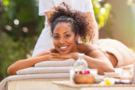 Junge afrikanische Frau, die Spa-Massage im Freien in einer tropischen Umgebung erhält. Glückliche Frau, die auf dem Bauch auf Massagetisch liegt und Schönheitsbehandlung zurückbekommt. Schönes Mädchen, das Massage und Spa-Behandlung in natürlicher Umgebung macht.
