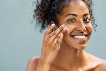 Schöne afroamerikanische Frau mit glatter Haut, die Feuchtigkeitscreme auf ihre Wange auftragen. Junge Frau der Schönheit, die sich um Haut kümmert. Glückliches Mädchen, das kosmetische Feuchtigkeitscremebehandlung einzeln auf Hintergrund anwendet und Kamera mit Kopienraum betrachtet. Standard-Bild