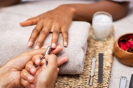 Close up of manicurist hands clipping client nails in a luxury spa. Young woman getting manicure treatment with hands kept on towel. Clipping nails, hand care and nailcare at beauty salon. Foto de archivo